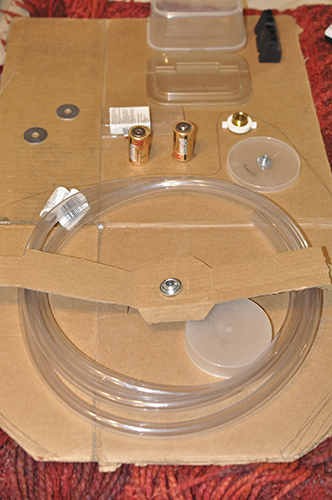 Cardboard box flat on ground with household items such as batteries and tubes laying on it to see how they work.