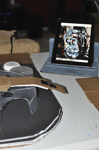 Picture of proton pack in progress, with an ipad propped up on a table, using a photo for inspiration.