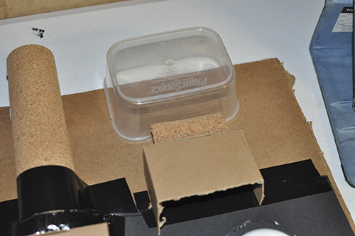 More items shown on top of the cardboard backing. A deli meat container, a box and a cork roll.