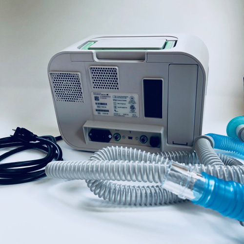 Photo of the back of the medical device, Philips Respironics Cough Assist T70, about the size of a big toaster, with a display screen and hose, with power cord