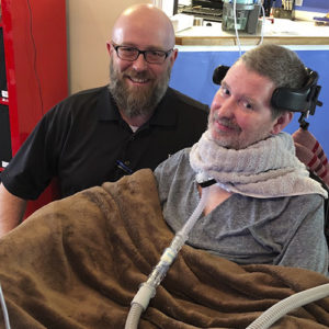 Photo of a bearded man who is respiratory therapist, kneeling next to a paralyzed man with ALS that has a trach
