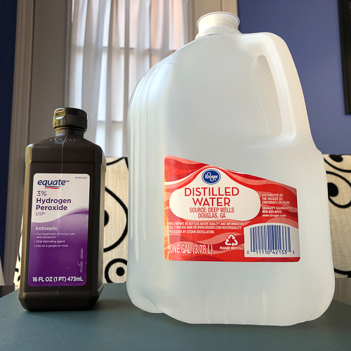 Photo of a bottle of peroxide and gallon of distilled water, sitting side by side on a table.