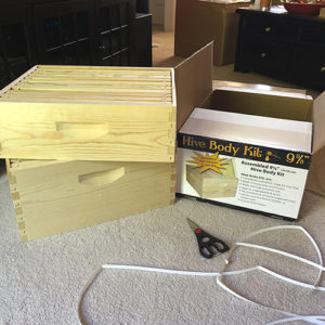 Photo of boxed beehive next to unboxed beehive box