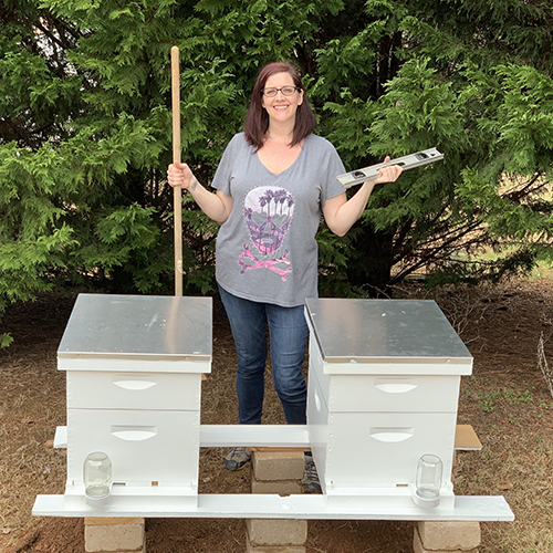 Photo of the author, Jen, behind behinves, with shovel and level in hands.