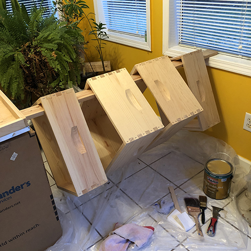 Photo of four wooden beehive frames, resting on a board, prepped to be painted.