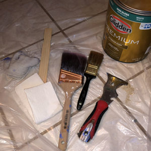 Photo of a can of Glidden premium exterior paint, two paint bruses, a five way tool, a wooden paint stirrer and plastic laid out in prep to paint.