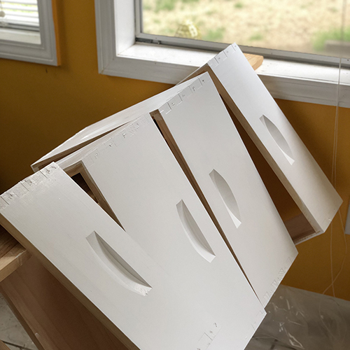 Photo of the four beehive wooden frames, as they were ready to be painted, now all freshly painted white.