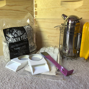 Photo of beehive accessories including smoker, hive tool and smoker fuel
