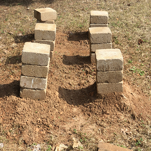 Photo of 6 columns of pavers, stacked 3 or so high. Photo shows that one column is leaning a bit, indicating that beehives would not be stable there yet.